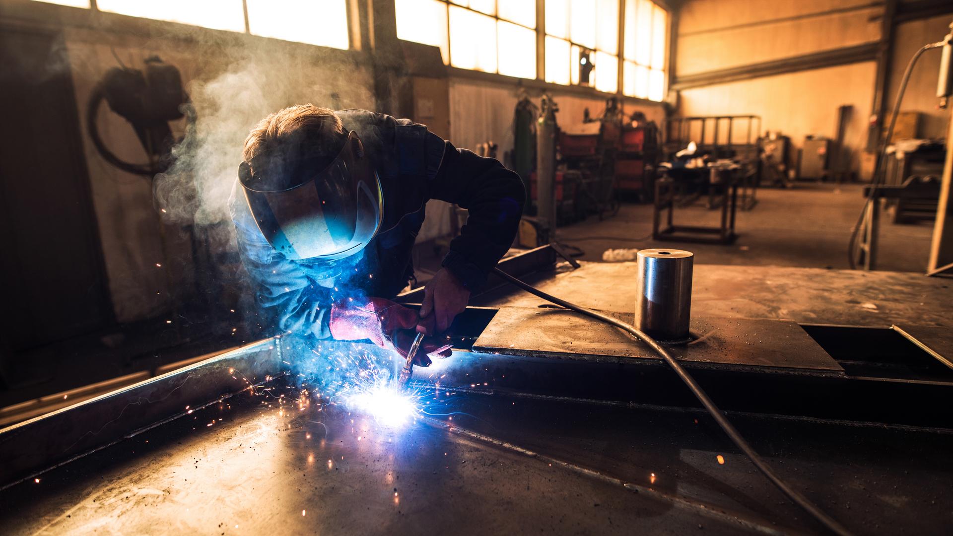 Professional welder in protective uniform and helmet welding metal part in workshop.