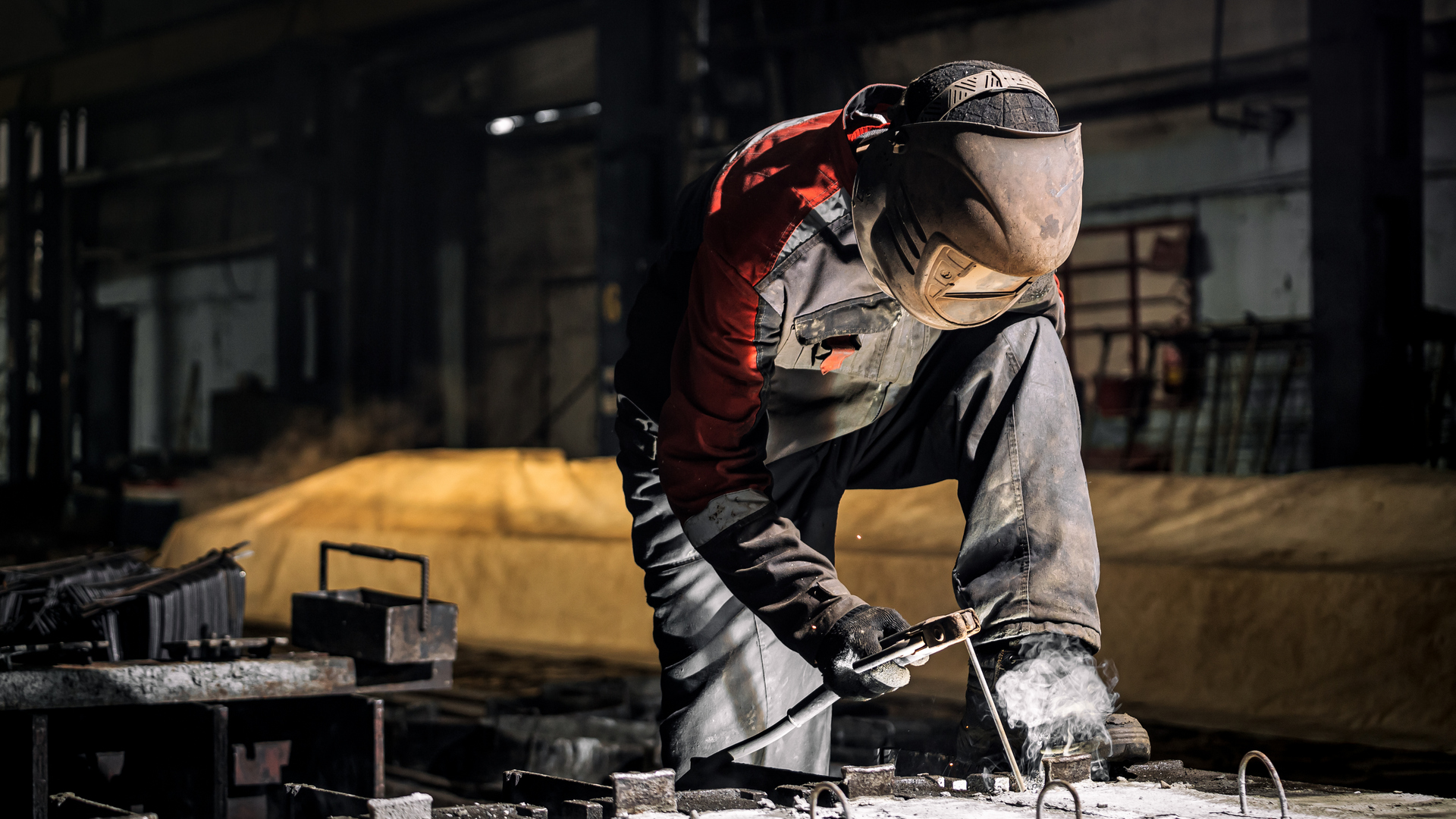 A young  man welder in  uniform, welding mask and welders leathers, weld  metal  with a  welding machine at the construction site, white smoke